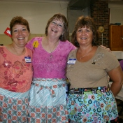Nancy Krueger, Bonnie Hunter, and Sue Peggs show off the cute aprons made by Sue.
