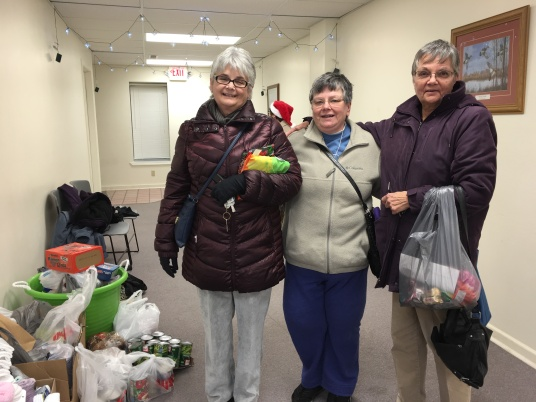 Kathy Krog, Kay Beach, Ceclia Riggle collecting food donations.