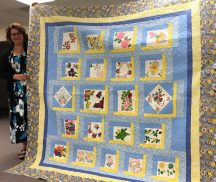 Andrea O'Brien and the final quilt made from hand-painted blocks.
