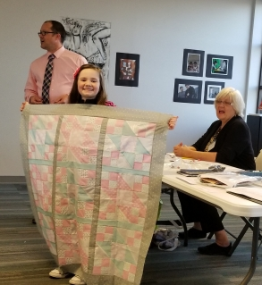 Macy Nunan and the quilt Meredith helped her with.