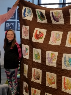 Macy Nunan and a quilt made by her great-great grandmother.